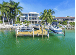 Upper Keys luxury homes for sale slide show. Photo of house on the waterfront with a wood pier, boat lift, landscaped backyard.