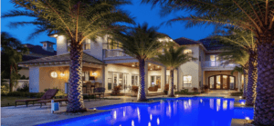 Night picture of lighted house, pool,and landscaping around a pool