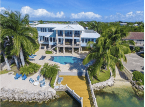Upper Keys luxury homes for sale slide show of home with pool, wooden pier, and sandy beach.
