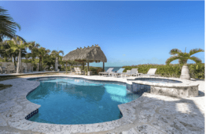 Upper Keys luxury homes for sale slide show. Back yard with pool, tiki thatch roof, and the ocean in the background.